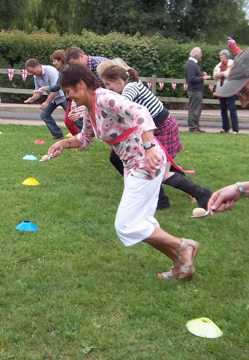 4 people having an egg race at a sports day