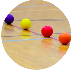 4 coloured balls positioned on the floor in a indoor sports hall