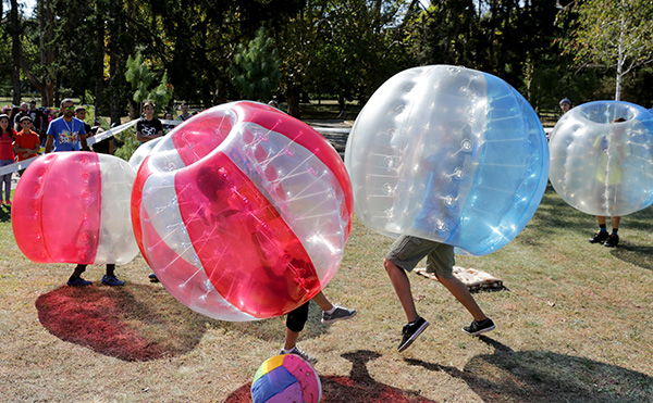 two women in inflatable bubble ball in a London park
