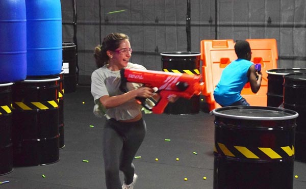 girl running with a nerf gun shooting plastic bullets