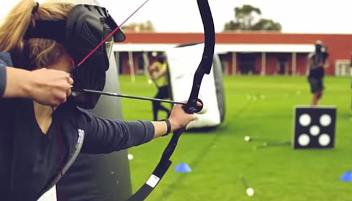 male holding a bow and arrow whilst aiming at a target